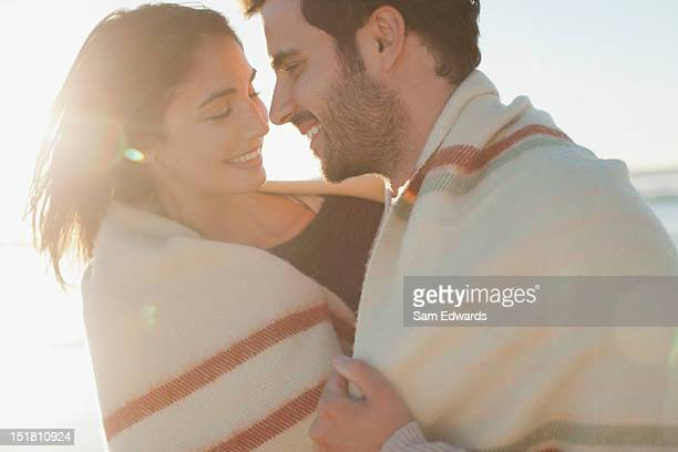 Smiling couple wrapped in blanket and hugging on beach