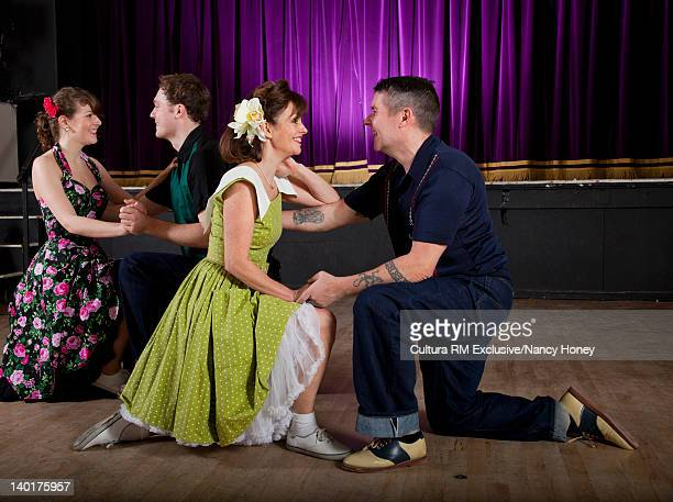 Smiling couples dancing in auditorium