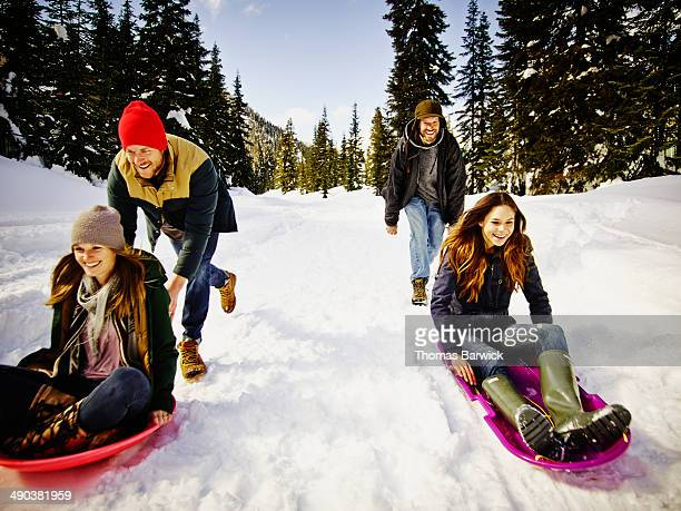 Smiling couples sledding down snowy road in forest