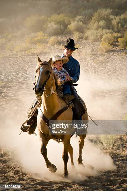 Smiling cowboy and son riding horse towards camera