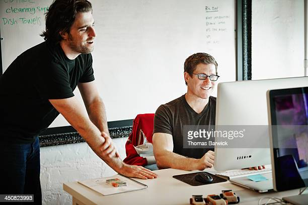 Smiling coworkers discussing project on computer