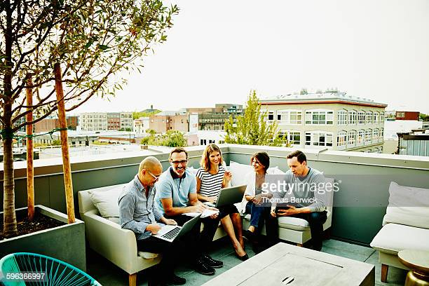 Smiling coworkers having meeting on office terrace