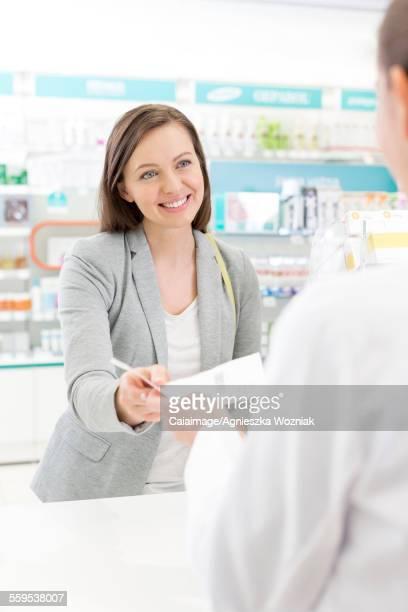 Smiling customer giving prescription to pharmacist in pharmacy