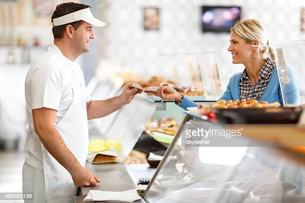 Souriant Client payant dans une boulangerie.