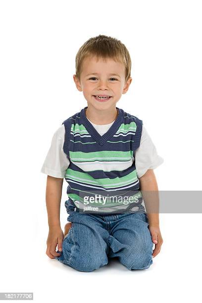Smiling cute little boy kneeling on white background