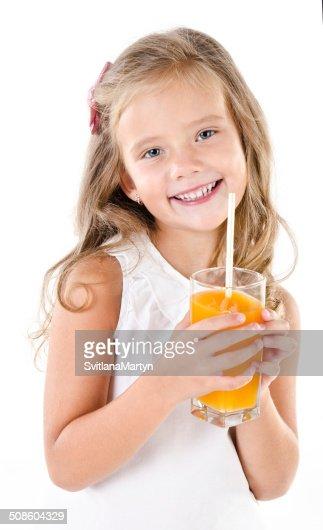 Sonriendo linda niña con vaso de jugo de frutas aisladas : Foto de stock