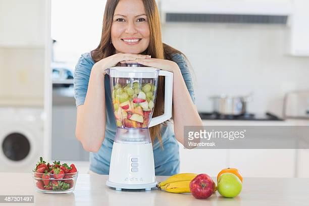 Souriant jolie femme posant avec un mixeur de cuisine
