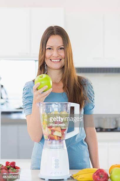 Jolie femme souriant avec un mixeur de cuisine