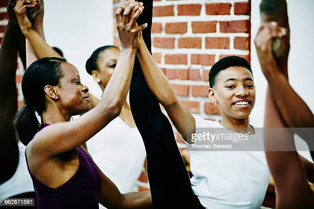 Smiling dance instructor adjusting students form
