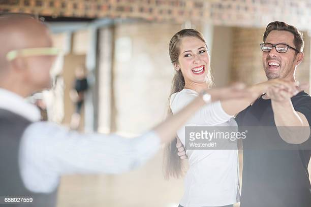 Smiling dance partners together in dance class with instructor
