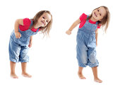 Happy toddler girl wearing jeans jumpsuit is having a great time dancing in the studio. Isolated on white..
