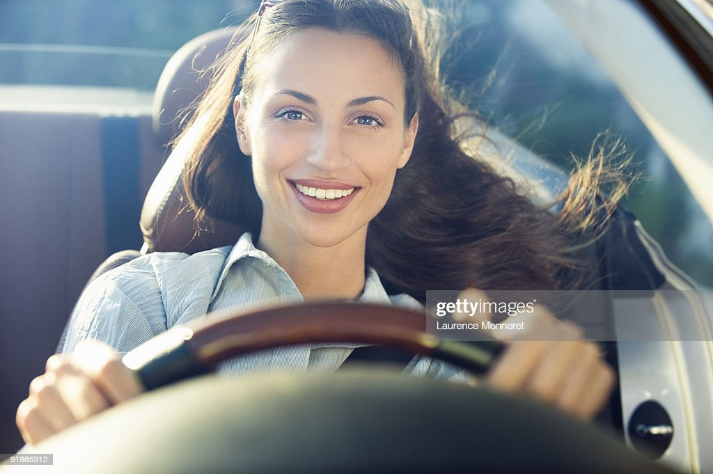 Smiling dark-haired woman driving a convertible : Stock Photo