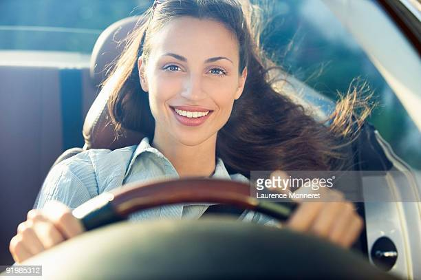 Smiling dark-haired woman driving a convertible