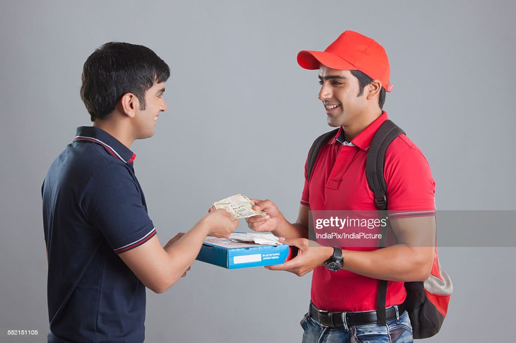Smiling delivery man delivering pizza to customer against gray background : Photo