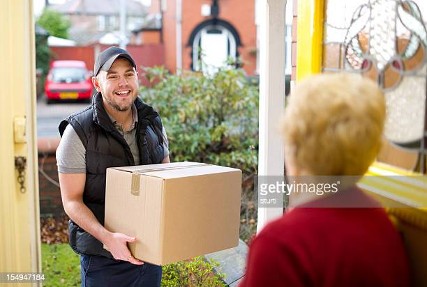 Smiling delivery man gives gran her parcel