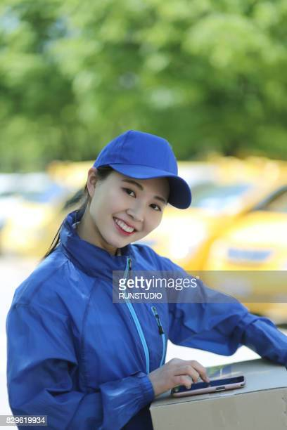 smiling delivery woman using smart phone