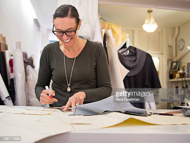 Smiling designer draws up garment panel