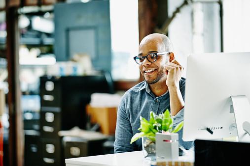 Smiling designer sitting at workstation in office