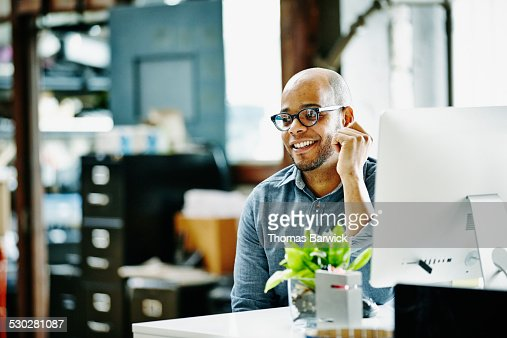 Smiling designer sitting at workstation in office