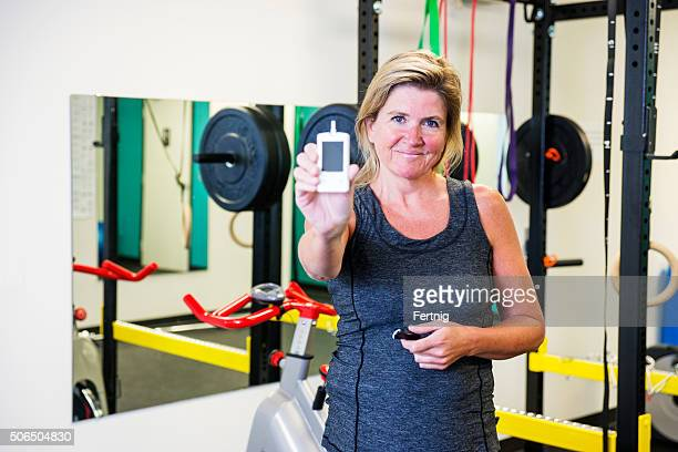Smiling diabetic woman checking her blood sugar in the gym