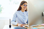 Smiling female graphic designer using mouse, stylus and tablet next to her on wooden desk in small office