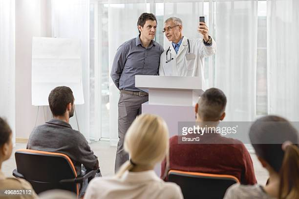 Smiling doctor and businessman taking a selfie on education event.