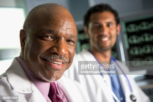 Smiling doctor and radiologist in front of MRI monitor screens : Stock Photo