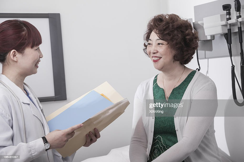 Smiling doctor holding a medical chart and consulting with a patient : Stock Photo