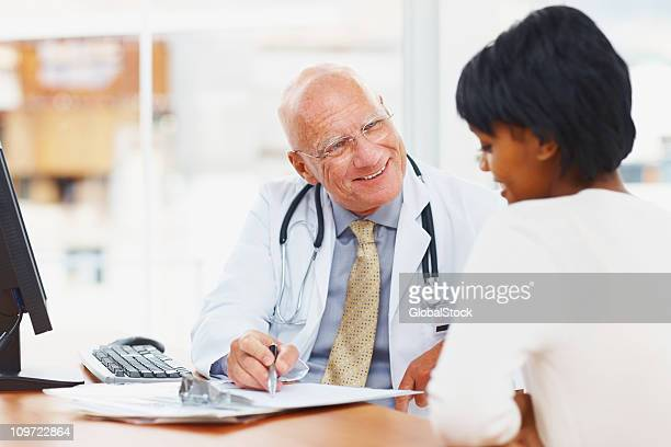 Smiling doctor showing medical reports to his patient