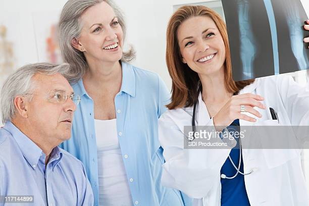 Smiling Doctor Showing X-Ray Results to Mature Adult Couple