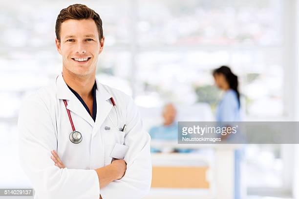 Smiling Doctor Standing Arms Crossed In Hospital