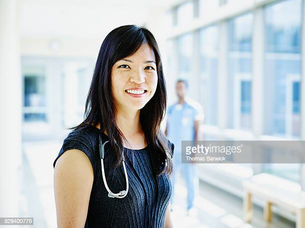Smiling doctor standing in hospital corridor