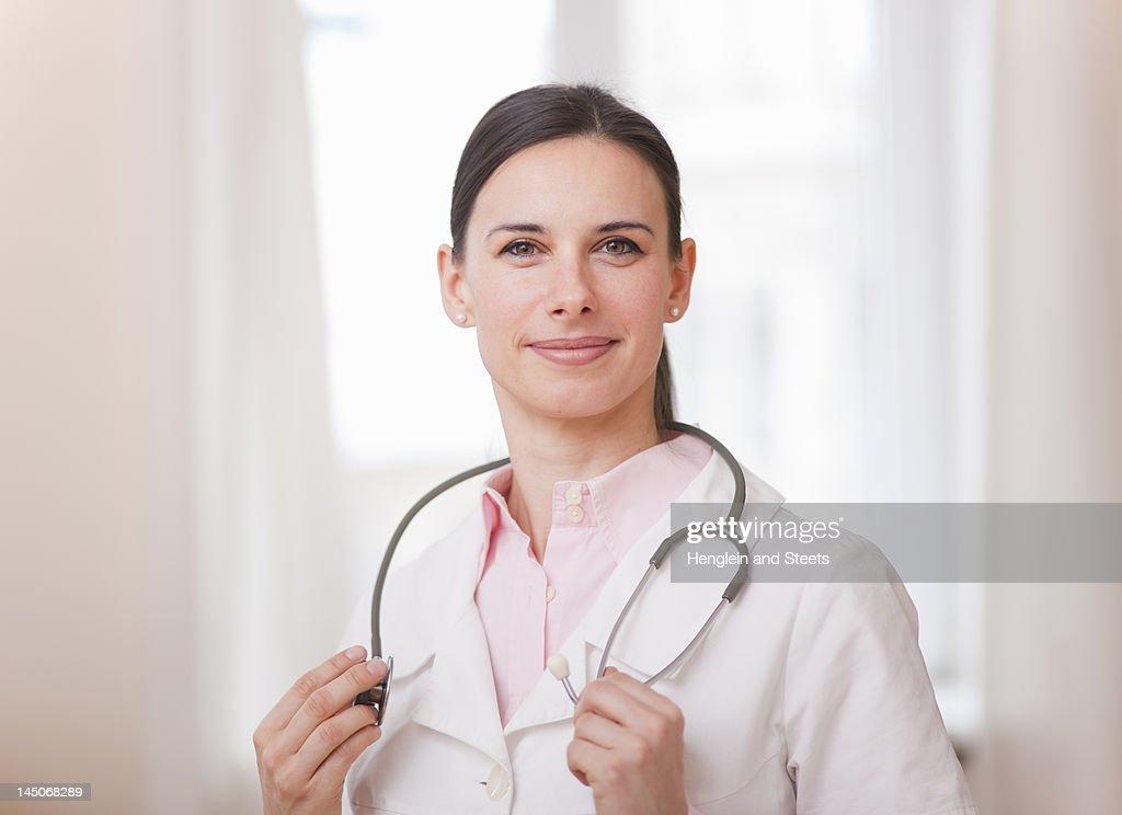 Smiling doctor wearing stethoscope : Stock Photo