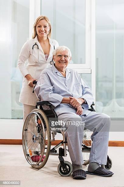 Souriant médecin avec le patient senior en fauteuil roulant.
