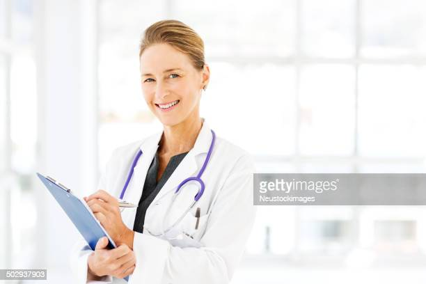 Sonriendo Doctor Writing On Clipboard In Hospital