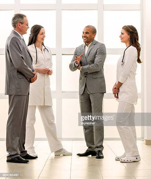 Smiling doctors and business people talking to each other.