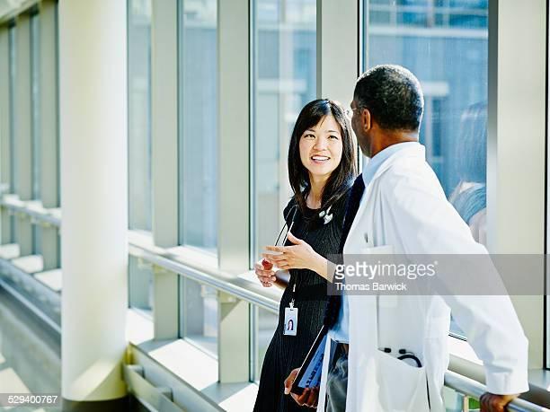 Smiling doctors in discussion in corridor