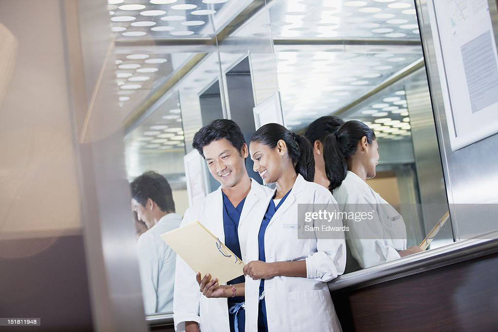 Smiling doctors reviewing medical record in hospital elevator : Stock Photo