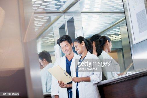 笑顔の医師の医療記録の検証の病院のエレベーター : ストックフォト
