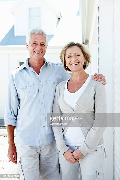Smiling elderly couple standing together while outdoors