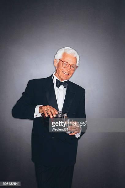 Smiling elegant senior man pouring drink into tumbler