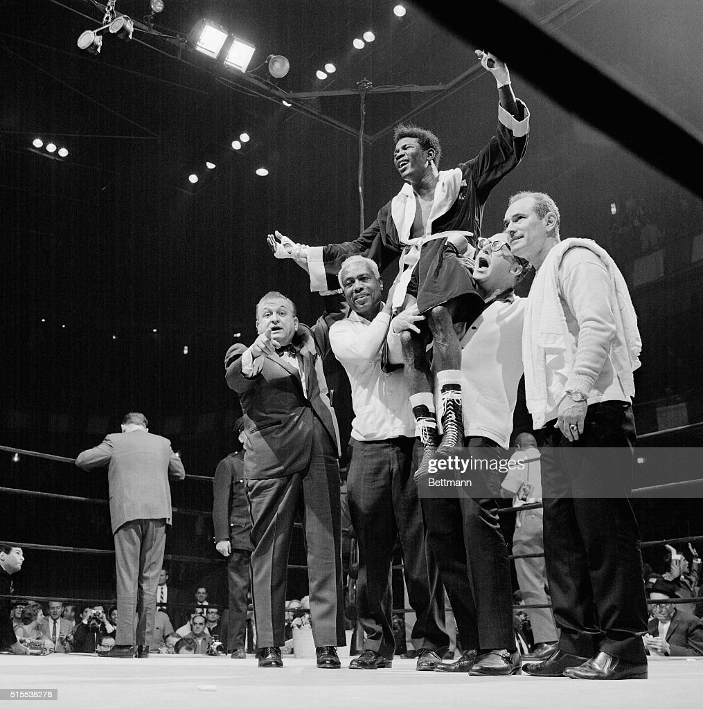 A smiling Emile Griffith gets a victory lift by his handlers after gaining a 15round decision over middleweight champion Dick Tiger at Madison Square...