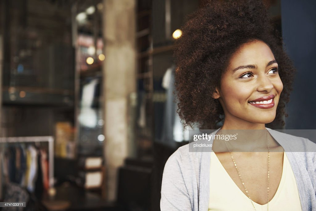 Smiling ethnic woman standing outside coffee house : Stock Photo