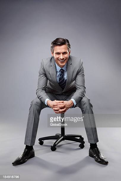 Smiling executive sitting on a stool