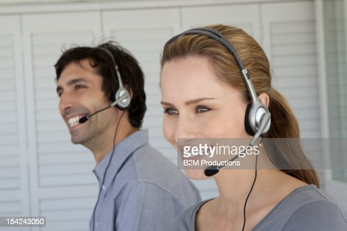 Smiling executives with headsets : Stock Photo
