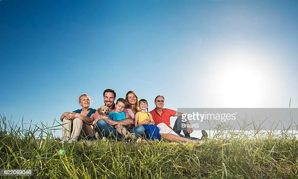 Smiling extended family enjoying in sunny day on grass.