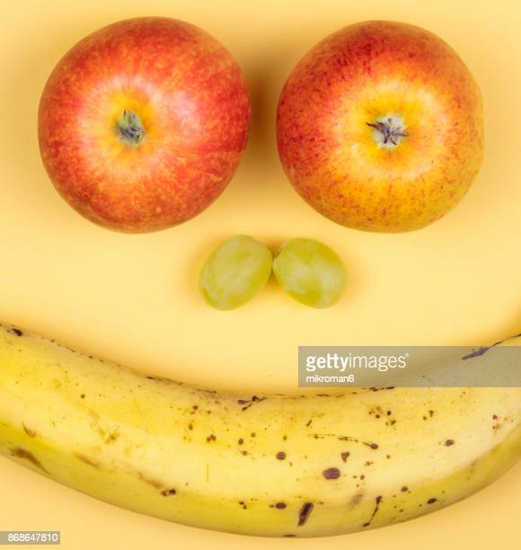 Smiling face made with apples, grapes and banana fruits