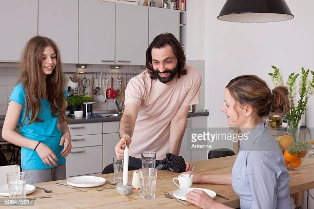 Smiling family arranging dinner table in kitchen