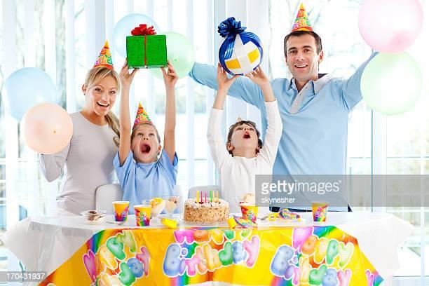 Sorridente famiglie festeggia il compleanno di bambini.