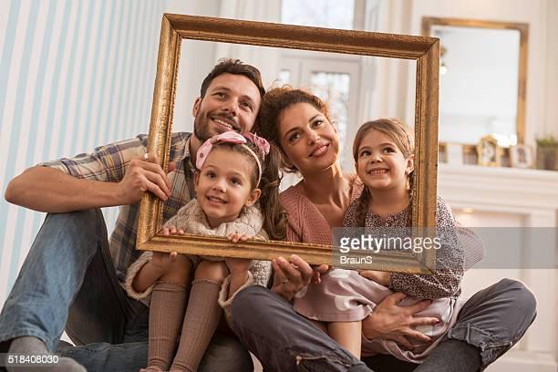 Sorridente famiglia divertirsi con una cornice per foto un casa.